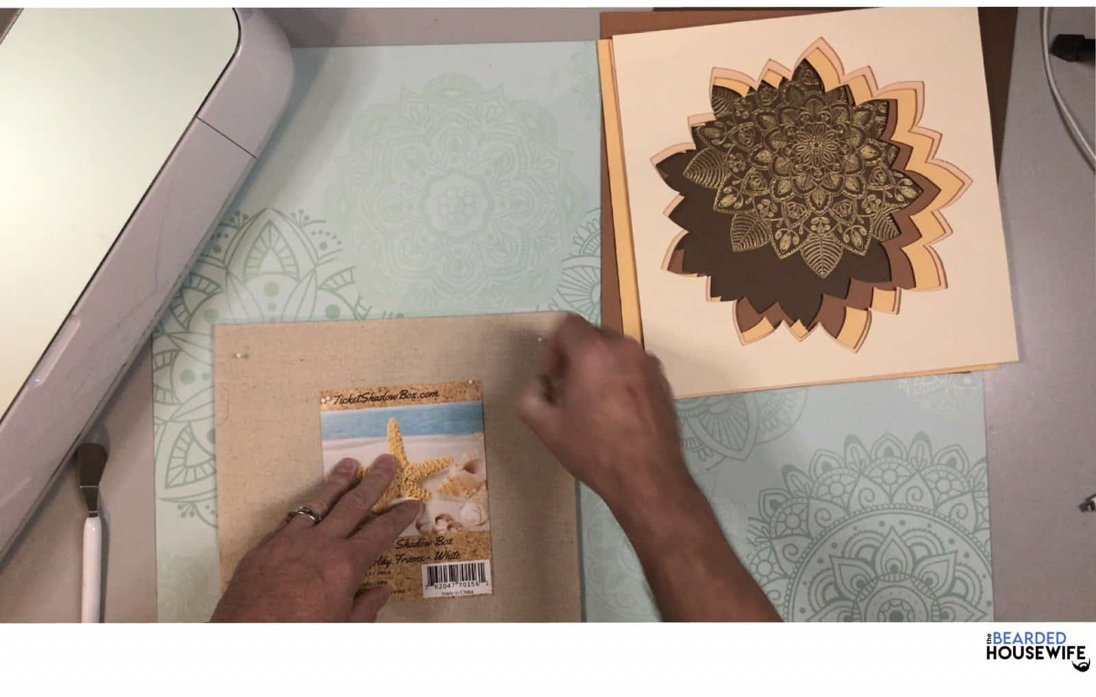 insert push pins into the fabric backing of your shadow box