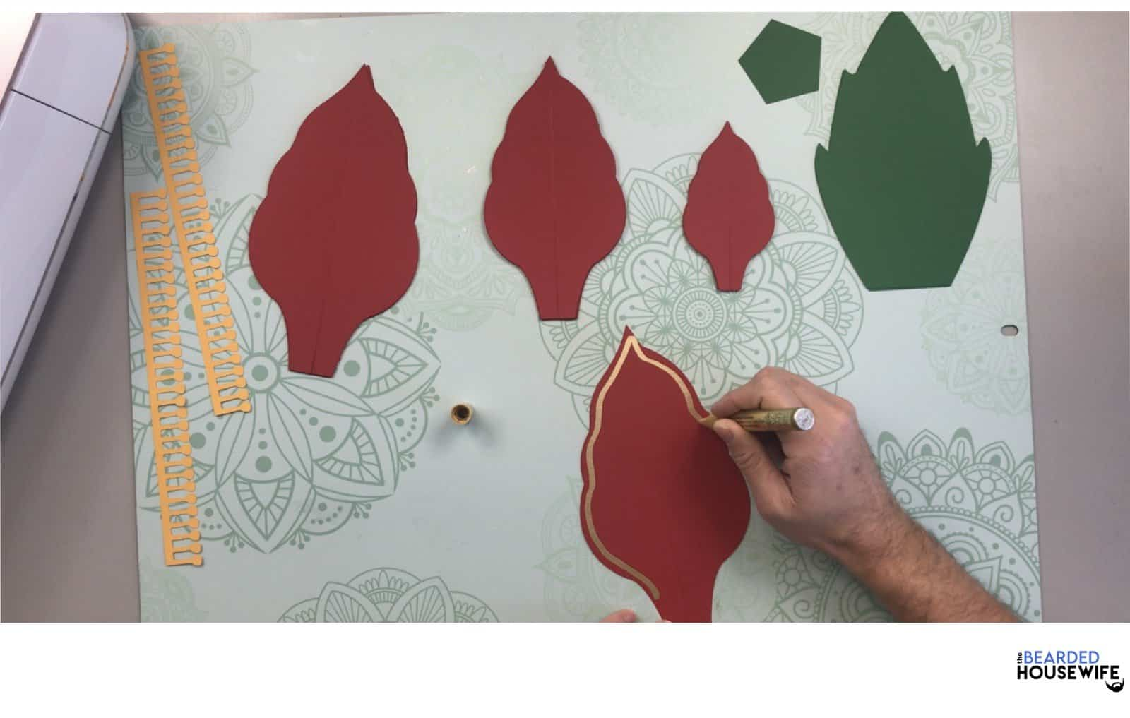 draw a line along the edge of your poinsettia leaves using the gold paint pen