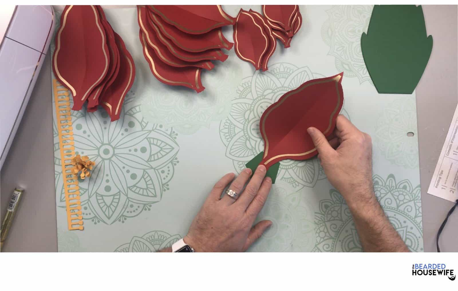 begin layering the poinsettia petals by adding hot glue to the back of one of the larger petals and placing on one side of the pentagon base.