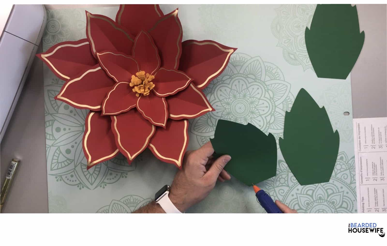 add hot glue to the bottom edge of the leaves