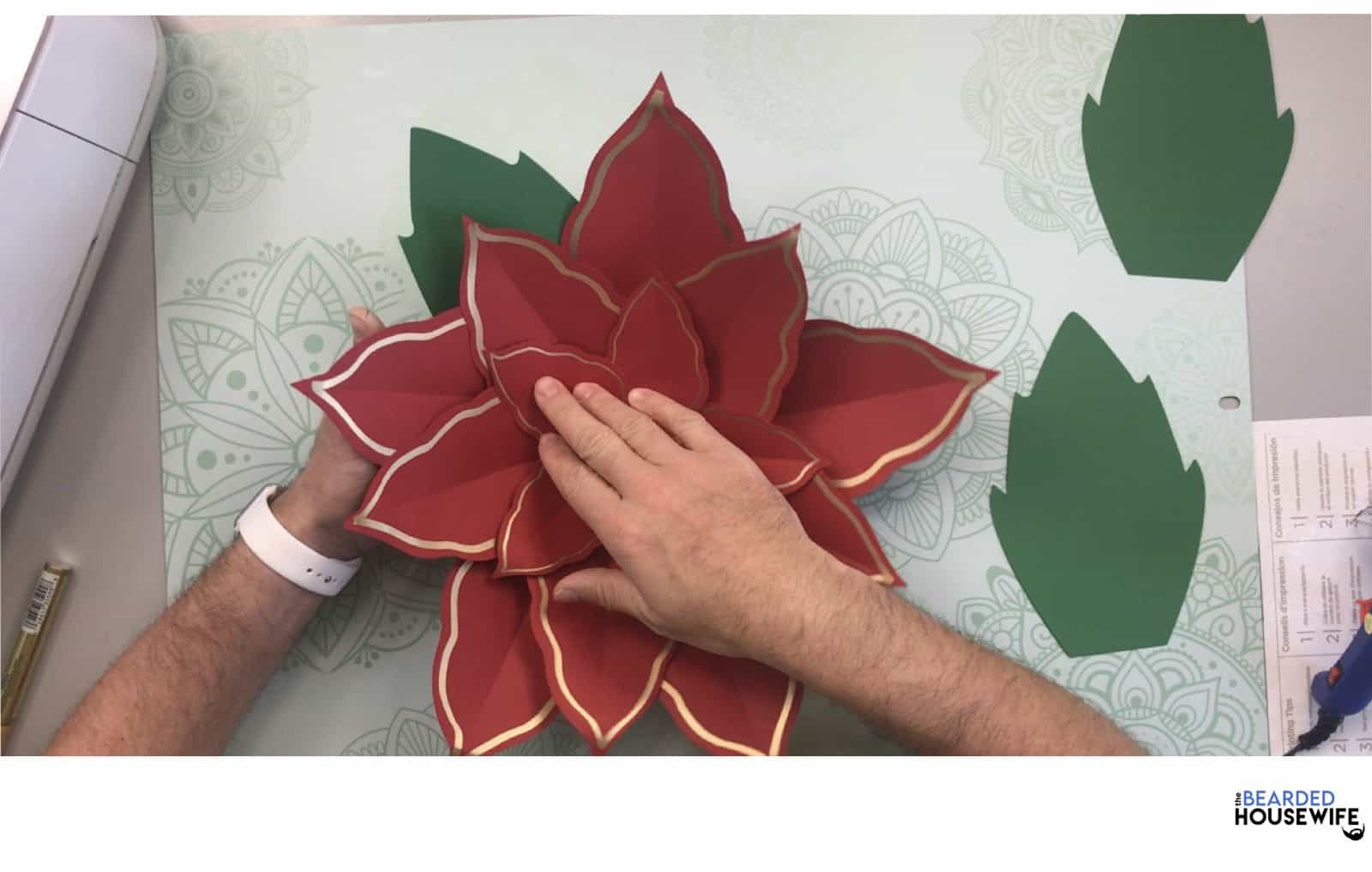 place behind the poinsettia flower and press into place with your hands