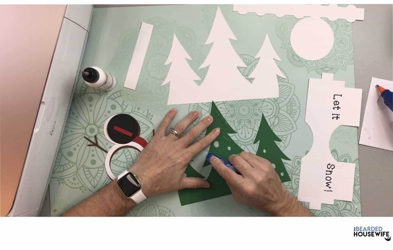 add adhesive to the back of the green pine trees