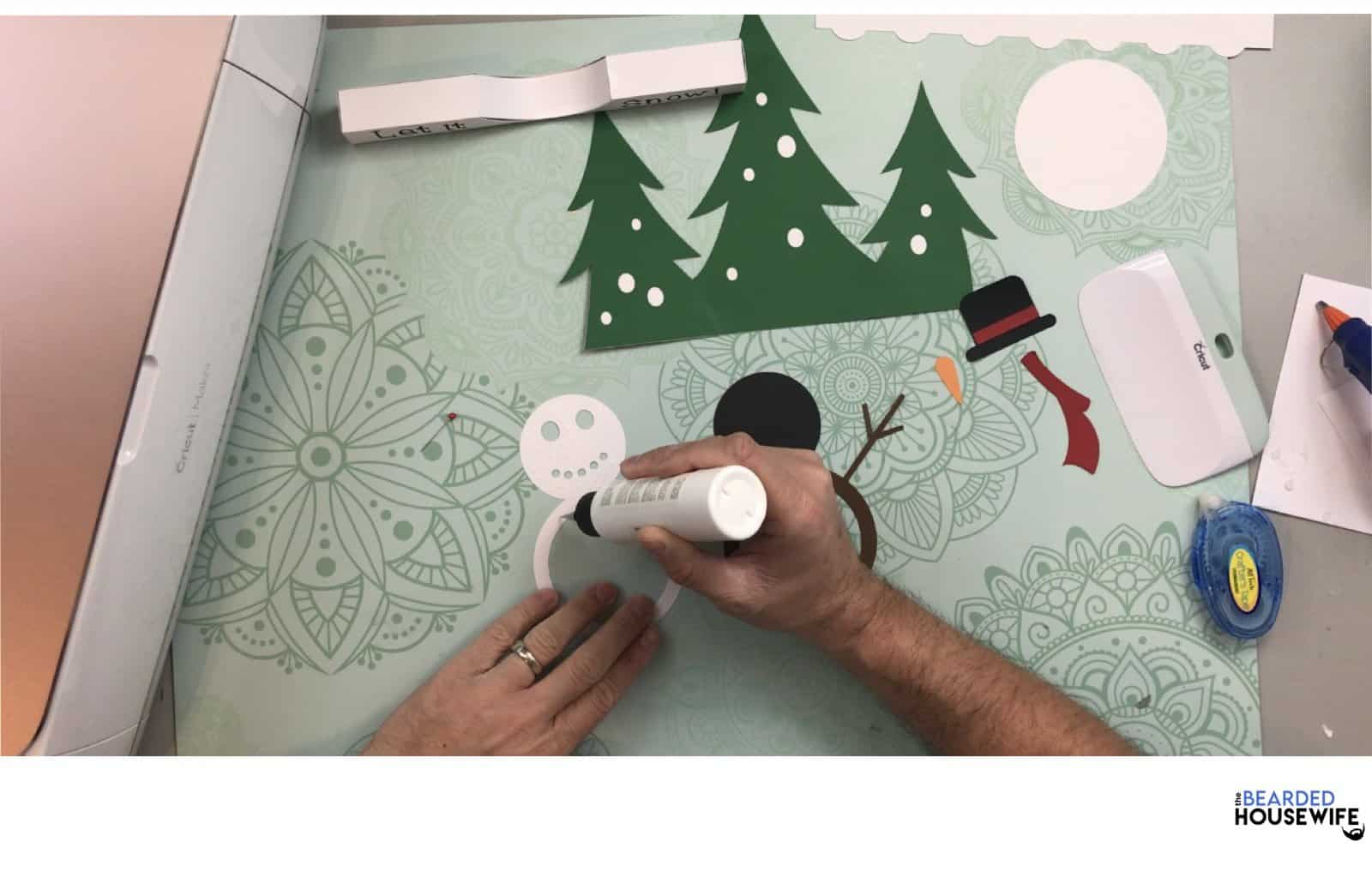 add glue to the back of the white snowman layer