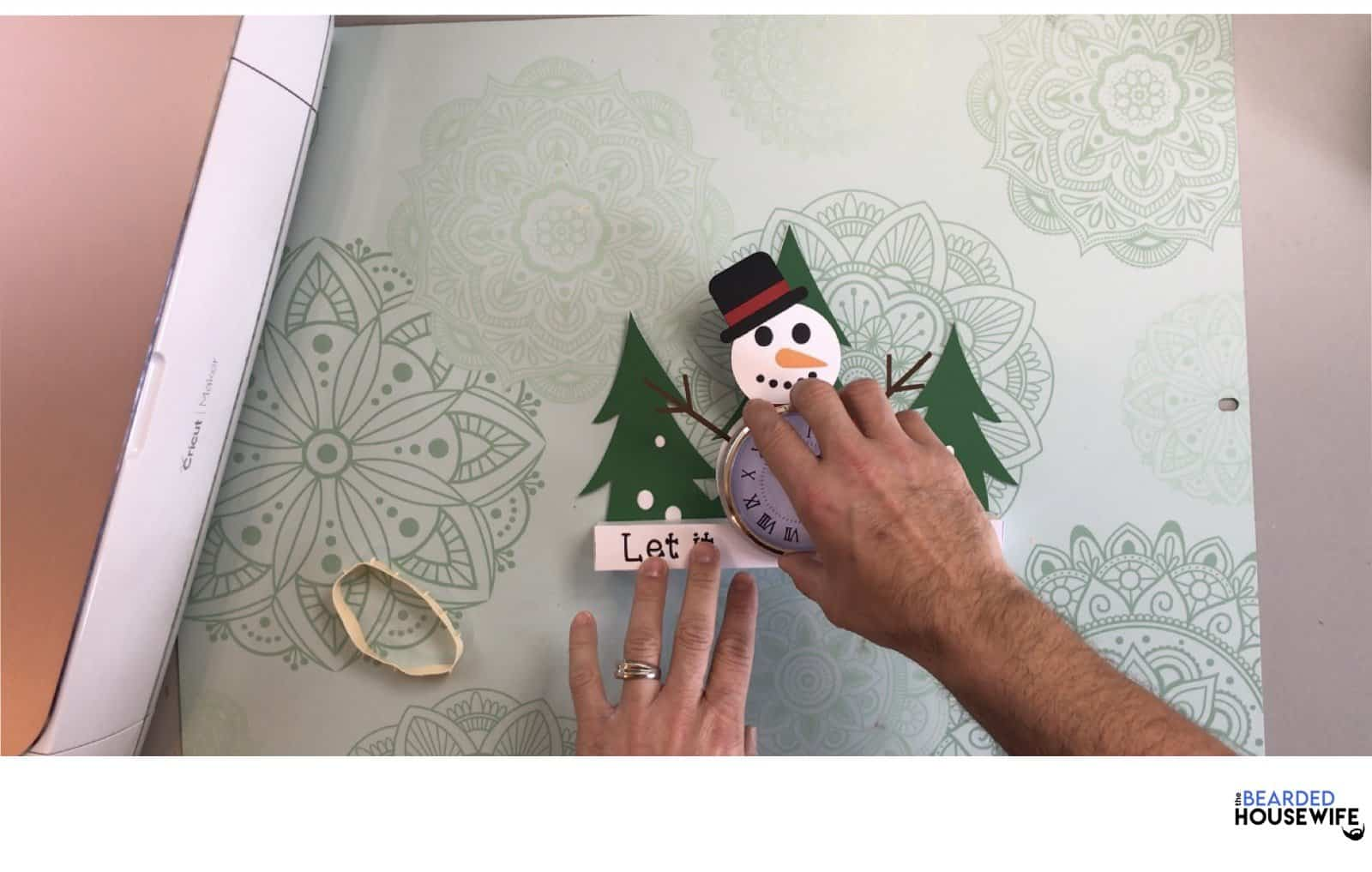 carefully insert the clock into the cavity in the snowman