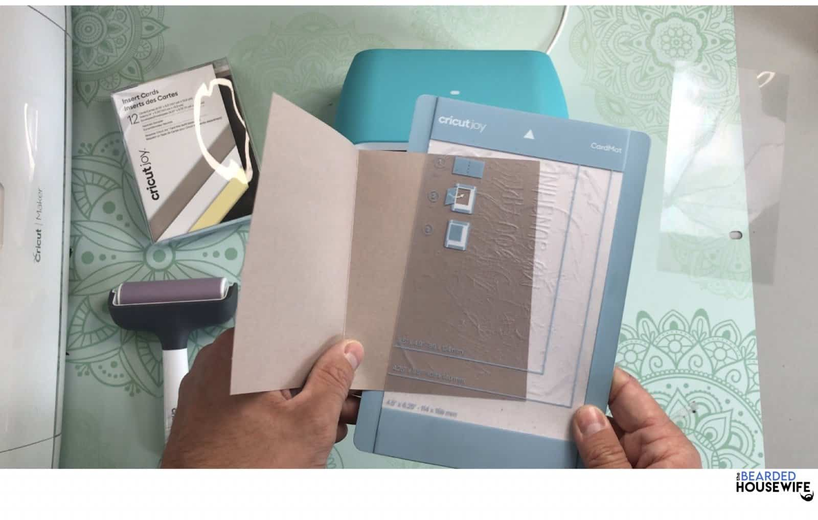 place the back of the card behind the sticky film of the card mat